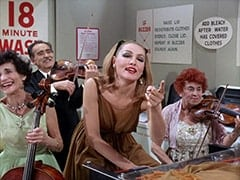 Cellist (?), Male Violinist (?), April Conquest (Julie Newmar), Female Violinist (?)